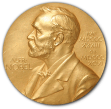 "A golden medallion with an embossed image of Alfred Nobel facing left in profile. To the left of the man is the text ""ALFR•"" then ""NOBEL"", and on the right, the text (smaller) ""NAT•"" then ""MDCCCXXXIII"" above, followed by (smaller) ""OB•"" then ""MDCCCXCVI"" below."